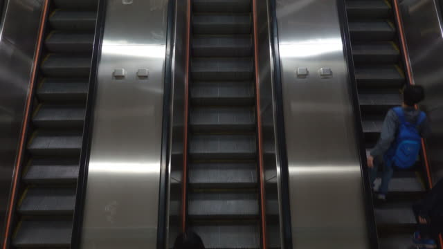 4k pedestrian, salaryman up and down the automatic escalator to travel to work and return home - ladder stock videos & royalty-free footage