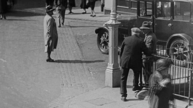 1930 ha pedestrian standing at busy intersection with traffic and other pedestrians rushing past / united kingdom - 1930 stock videos & royalty-free footage