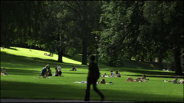 A pedestrian strolls past sunbathers at a park in Oslo, Norway.