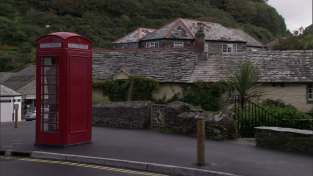 a pedestrian uses a red phone box in boscastle village. - pay phone stock videos and b-roll footage
