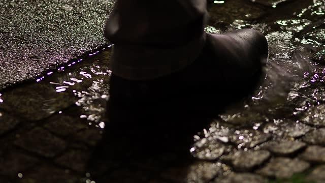 pedestrian walking through puddle on rainy sidewalk at night - cobblestone stock videos & royalty-free footage
