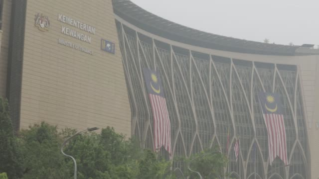 a pedestrian walks across putrajaya boulevard as the prime minister of malaysia's office stands shrouded in haze in the background in putrajaya... - putrajaya stock videos & royalty-free footage