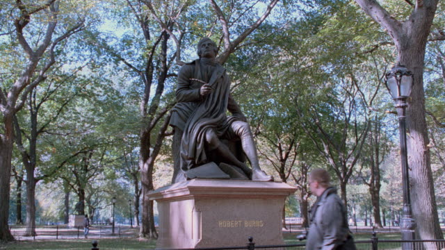 a pedestrian walks by a statue of robert burns in new york's central park. - robert burns poet stock videos & royalty-free footage