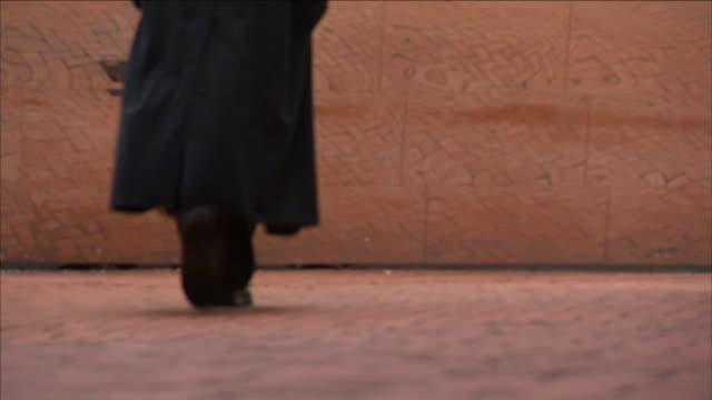 a pedestrian walks toward a reflective surface and then back again. - トレンチコート点の映像素材/bロール