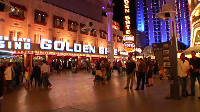 pedestrian walkway w/ unidentified people standing around outside golden gate casino smallest hotel on fremont street blue building bg - casino sign stock videos & royalty-free footage
