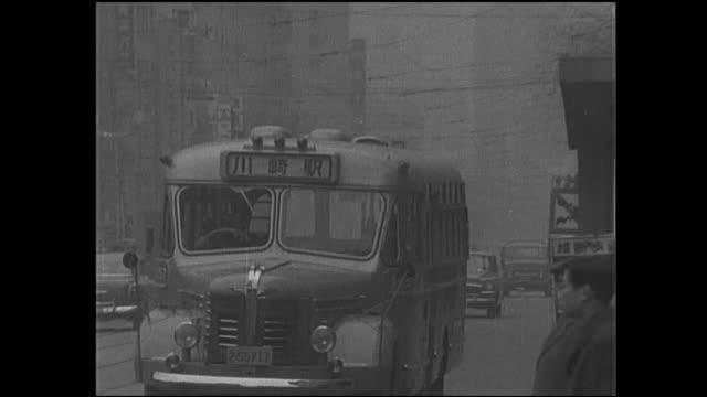 vídeos de stock e filmes b-roll de a pedestrian watches a bus pass as traffic moves through a haze on chuo-dori. - 1950 1959