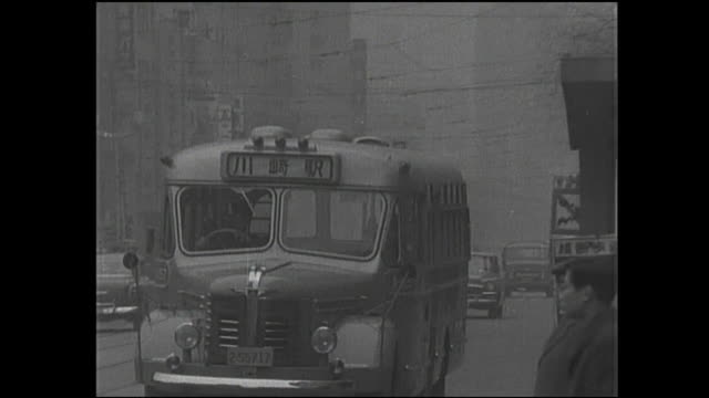a pedestrian watches a bus pass as traffic moves through a haze on chuo-dori. - 1950 1959 video stock e b–roll