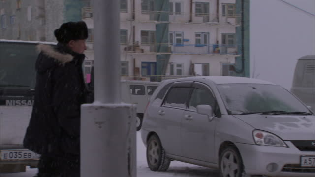 a pedestrian wearing a winter coat walks through a parking lot during a snow storm past two men shoveling snow. - cappotto invernale video stock e b–roll