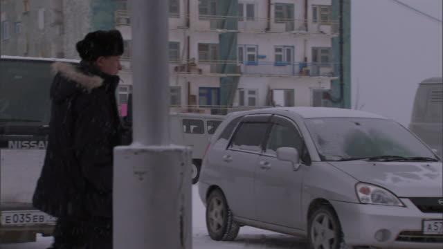vídeos y material grabado en eventos de stock de a pedestrian wearing a winter coat walks through a parking lot during a snow storm past two men shoveling snow. - abrigo de invierno