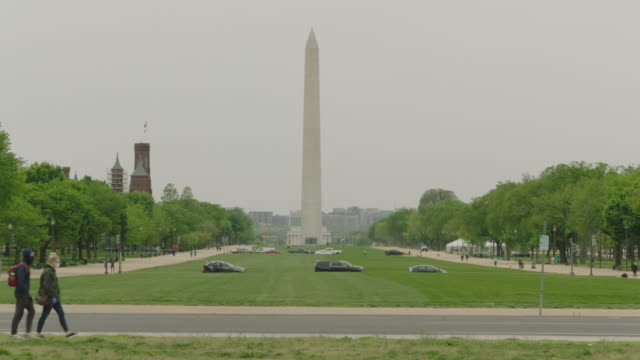 vídeos de stock e filmes b-roll de pedestrian wearing mask walk with washington monument in the background - patriotismo