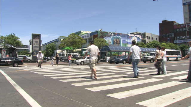 Pedestrians and a cyclist cross an intersection in Jeju, Republic of Korea.