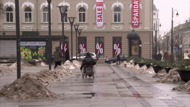pedestrians and a man in a wheelchair dodge piles of snow on a sidewalk in siauliai. available in hd. - lithuania stock videos and b-roll footage