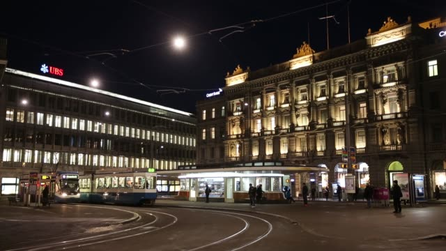 pedestrians and a tram pass ubs group ag left and credit suisse group ag's headquarters on paradeplatz in zurich switzerland on tuesday feb 10 2015 - hauptfirmensitz stock-videos und b-roll-filmmaterial