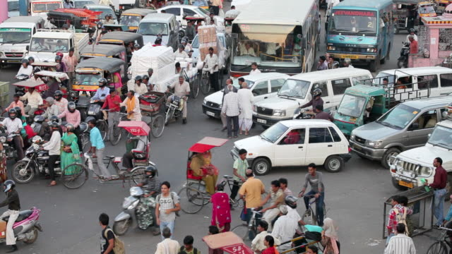 Pedestrians and bicyclists pass in between vehicles stopped on a busy street in Jaipur.