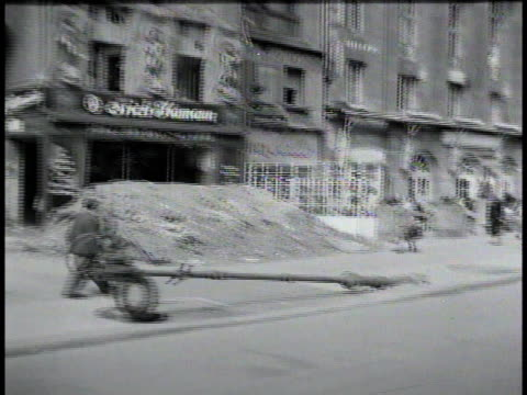 vídeos de stock, filmes e b-roll de pedestrians and bicyclists travel down wartorn street / berlin germany - 1945