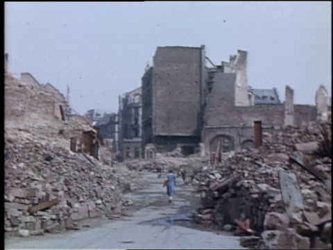 stockvideo's en b-roll-footage met ws pedestrians and bicyclists traveling down road between piles of rubble from bombed buildings / wiesbaden germany - geallieerde mogendheden
