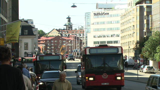 Pedestrians and buses crowd the sidewalks and streets in Stockholm, Sweden.