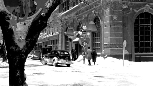 pedestrians and cars travel through a snowy intersection in a small town. - 1946 stock videos & royalty-free footage