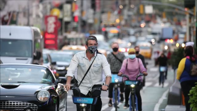 pedestrians and cyclists, some in face masks, traverse times square on october 19, 2020 in new york city. a state order requires everyone to wear a... - bicycle stock videos & royalty-free footage