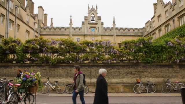 Pedestrians and cyclists travel past Sydney Sussex College, Cambridge.