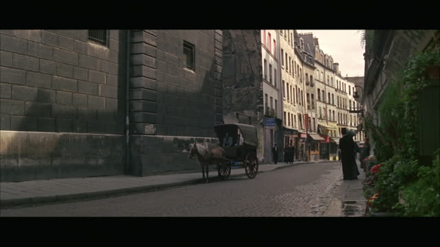 ws pedestrians and horse drawn carriage on old town street / paris, france - rievocazione video stock e b–roll