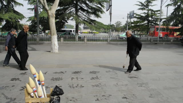 Pedestrians and motorists pass an artist who draws calligraphy on a park sidewalk.