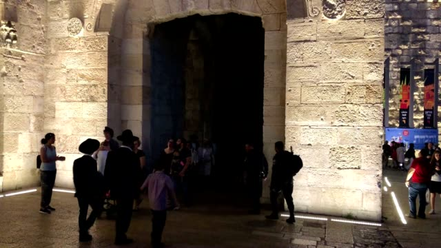 pedestrians and police move in and out of jaffa gate in the old city - israelisches militär stock-videos und b-roll-filmmaterial