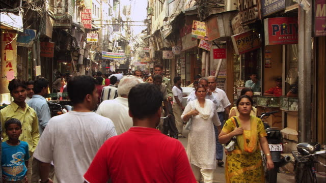 Pedestrians and shoppers move along a busy street in New Delhi. Available in HD.