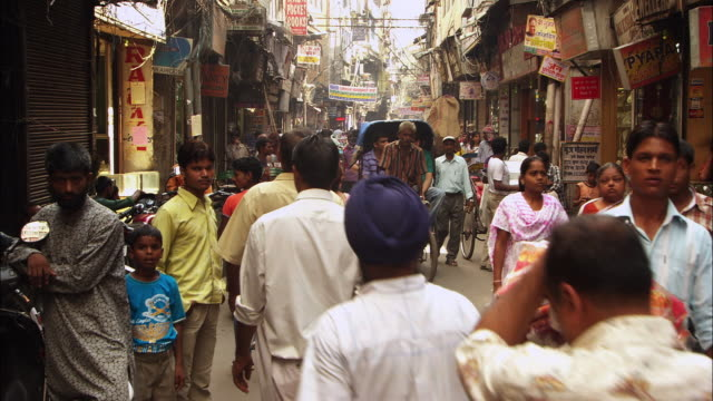 pedestrians and shoppers move along a busy street in new delhi. available in hd. - riksha bildbanksvideor och videomaterial från bakom kulisserna