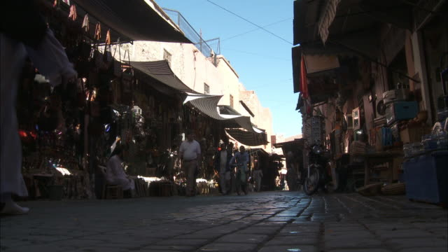 Pedestrians and shoppers move through a souk in Marrakech.