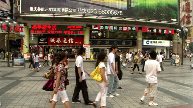 Pedestrians and shoppers pass multimedia jumbotrons. Available in HD.