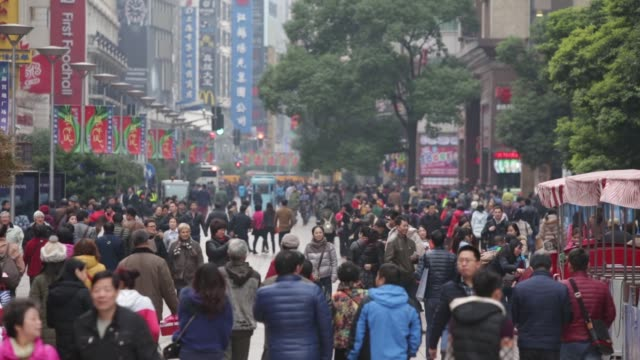 pedestrians and shoppers walk down nanjing road in shanghai, china, on saturday, dec. 5 shoppers enter and exit a department store in shanghai - nanjing road stock videos & royalty-free footage