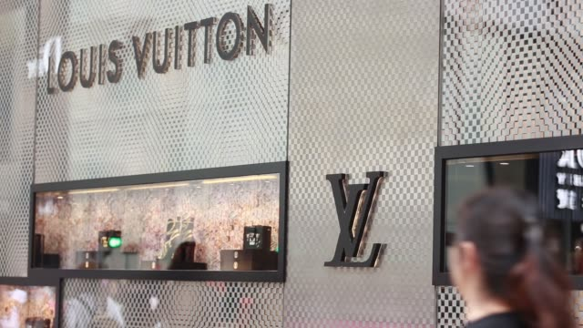 stockvideo's en b-roll-footage met mws pedestrians and shoppers walk past a louis vuitton store operated by lvmh moet hennessy louis vuitton sa on canton road signage for louis vuitton... - louis vuitton modelabel