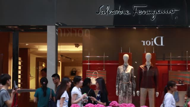 pedestrians and shoppers walk past a salvatore ferragamo store on canton road, shoppers line up outside a salvatore ferragamo store, logo for... - salvatore ferragamo stock videos & royalty-free footage