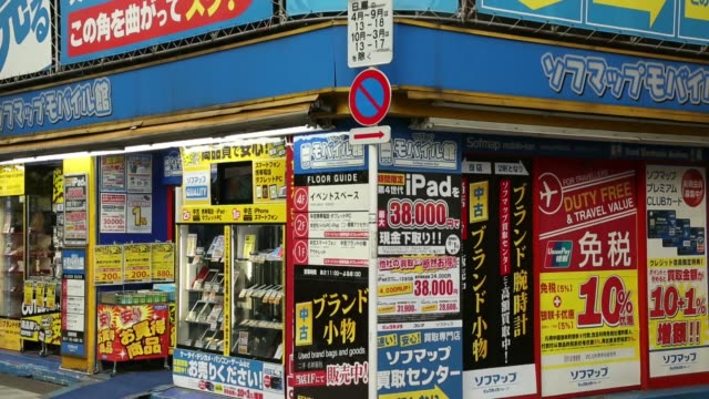 Pedestrians and shoppers walk past advertisements outside an electronics store in the Akihabara district in Tokyo Japan on Thursday Nov 14...