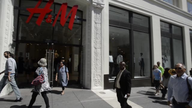 Pedestrians and shoppers walk past an Hennes Mauritz AB store in San Francisco California Close up shots of HM signage above the store entrance Wide...