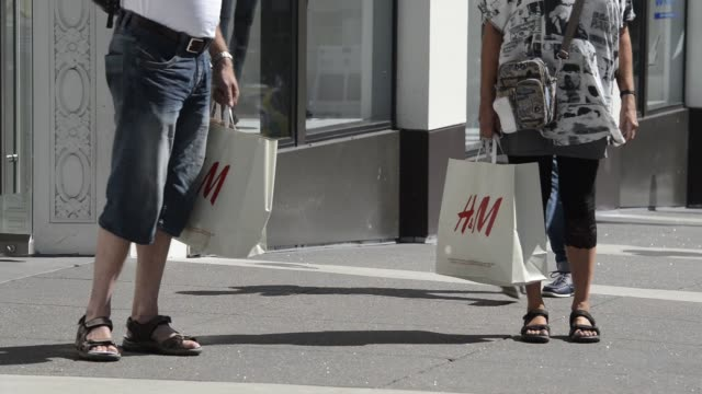 Pedestrians and shoppers walk past an Hennes Mauritz AB store in San Francisco California Shots focus on shoppers entering and leaving the store...