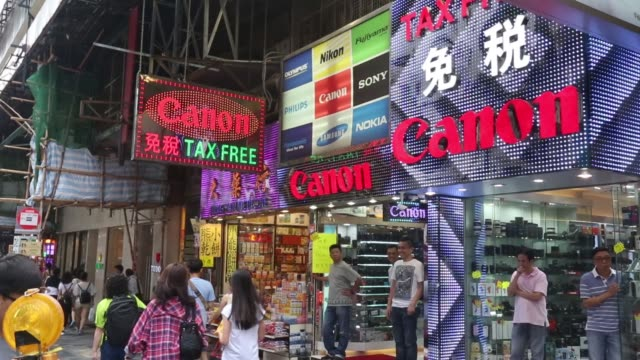 Pedestrians and shoppers walk past camera stores along Nathan Road in the Tsim Sha Tsui district of Hong Kong on Thursday Oct 1 Shoppers enter a...