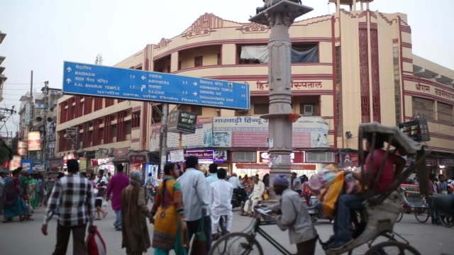 pedestrians and shoppers walk past stores on a street in varanasi uttar pradesh india on saturday oct 29 shoppers browse at a stall selling clothes... - uttar pradesh stock videos and b-roll footage