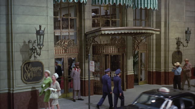 1967 ws zi cu pedestrians and street musicians walking in front of hotel entrance, st. gregory hotel sign on wall / new orleans, louisiana, usa - ornate stock videos and b-roll footage