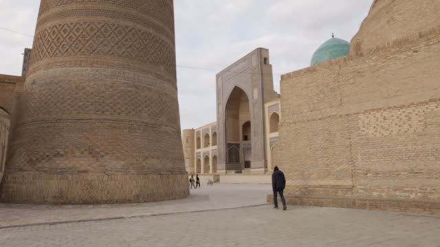 pedestrians and tourists at miriarab madrasa in the old city of bukhara uzbekistan on sunday march 11 photograph taylor weidman/bloomberg - bukhara stock videos & royalty-free footage