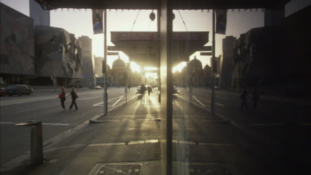 WS PAN Pedestrians and traffic along Federation Square at sunset, Melbourne, Victoria, Australia