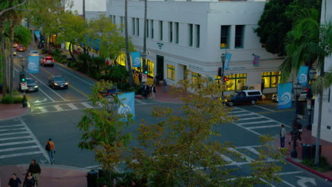 high angle wide shot pedestrians and traffic at intersection of canon perdido and state streets in downtown santa barbara, california at dusk - santa barbara california stock videos & royalty-free footage