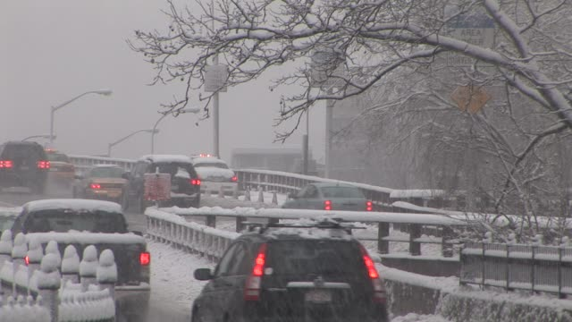 Pedestrians and traffic cross Brooklyn Bridge at the height of the snow storm Available in HD