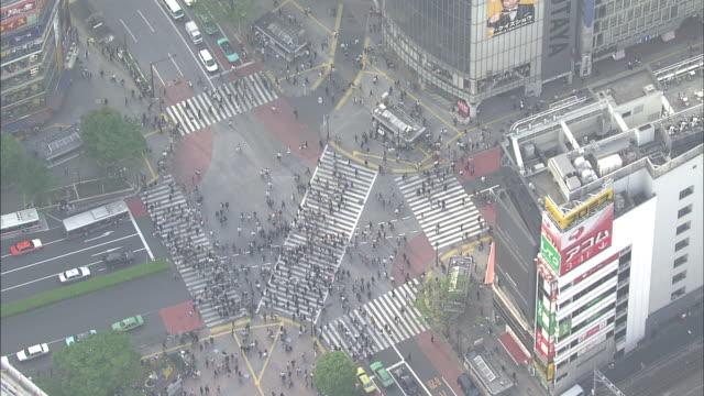pedestrians and traffic cross the shibuya scramble crossway in tokyo. - shibuya ward stock videos & royalty-free footage