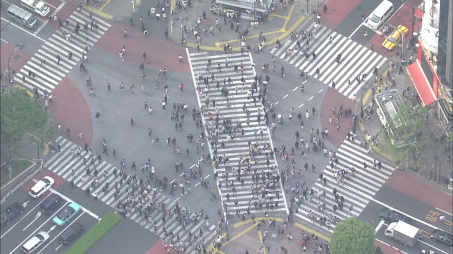 Pedestrians and traffic cross the Shibuya Scramble Crossway in Tokyo,