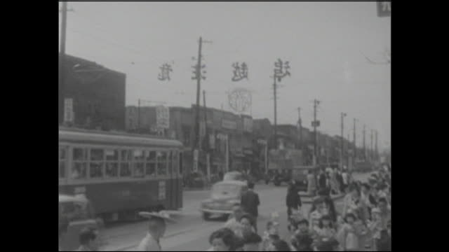 pedestrians and traffic crowd a street during the 500 year celebration of edo castle in tokyo, japan. - 1950~1959年点の映像素材/bロール