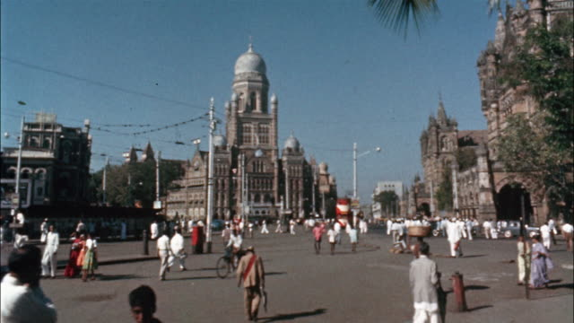 pedestrians and traffic crowd the busy streets of mumbai, india; motor scooters and bicycles drive past the indian parliament building in new delhi. - archival stock videos & royalty-free footage