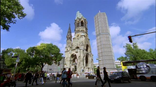 wide shot pedestrians and traffic in front of kaiser wilhelm memorial church on kufuerstendamm, berlin, germany - カイザー・ヴィルヘルム記念教会点の映像素材/bロール
