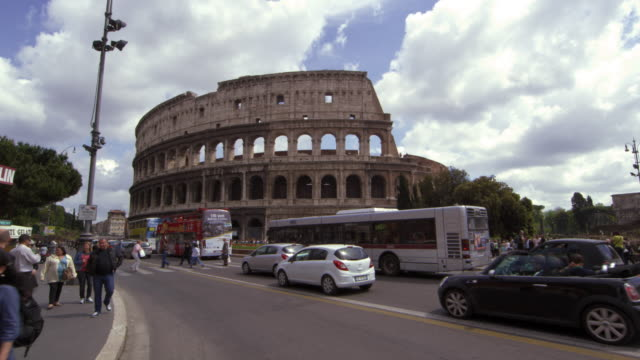 pedestrians and traffic in front of the colosseum in rome italy - colosseo video stock e b–roll